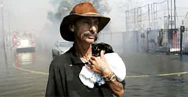 Robert Fonteaine holds his puppy as he watches New Orleans firefighters try to save his house. Photograph: Eric Gay/AP
