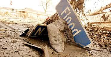 The street sign for Flood Street sits in the mud where it fell after Hurricane Katrina in New Orleans, Louisiana. Photograph: Brian Snyder/ Reuters
