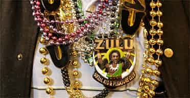 A reveller wear beads and a badge for the Zulu Social Aid and Pleasure Club as he celebrates Mardi Gras in New Orleans. Photograph: Dan Chung