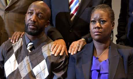The parents of Trayvon Martin, Sybrina Fulton and Tracy Martin, hold hands as they watch coverage of special prosecutor Angela Corey