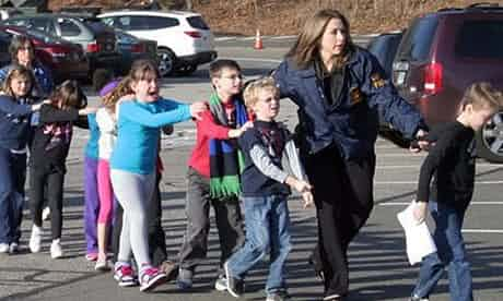 Connecticut state police lead children from the Sandy Hook elementary school. Photograph: Shannon Hicks/Newtown Bee