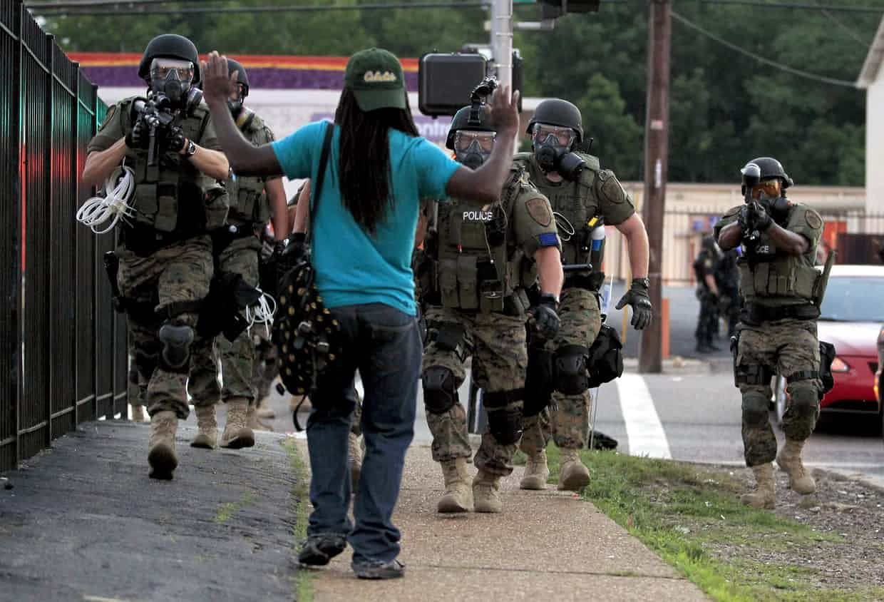 Police wearing riot gear walk towards a young black man in Ferguson, Missouri. Photograph: Jeff Roberson/AP