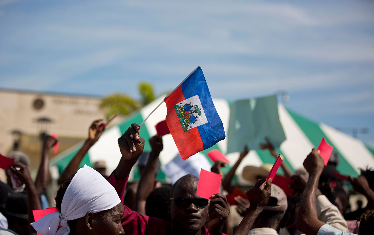 A Haitian holds a national flag outside the US embassy in Port-au-Prince on January 18, 2018, to protest President Donald Trumps comments.  ( AP Photo / Dieu Nalio Chery)